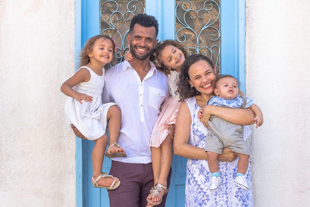 Leonardo e Carolina, na frente de uma porta azuil, com seus três filhos.