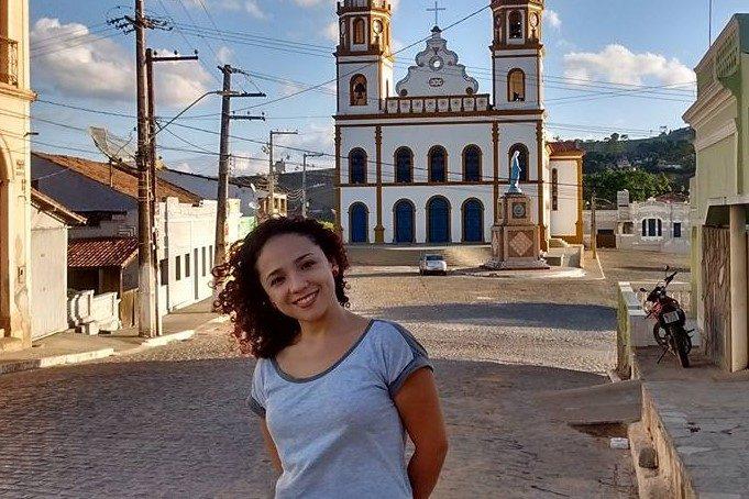 Lívia sorrindo em uma paisagem histórica