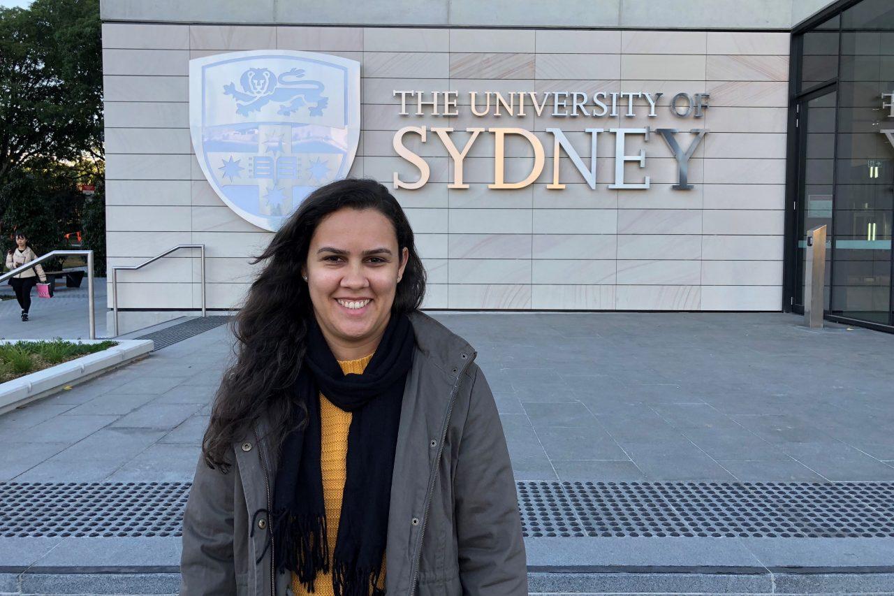 Foto da Shirley sorrindo, diante da universidade de Sidney