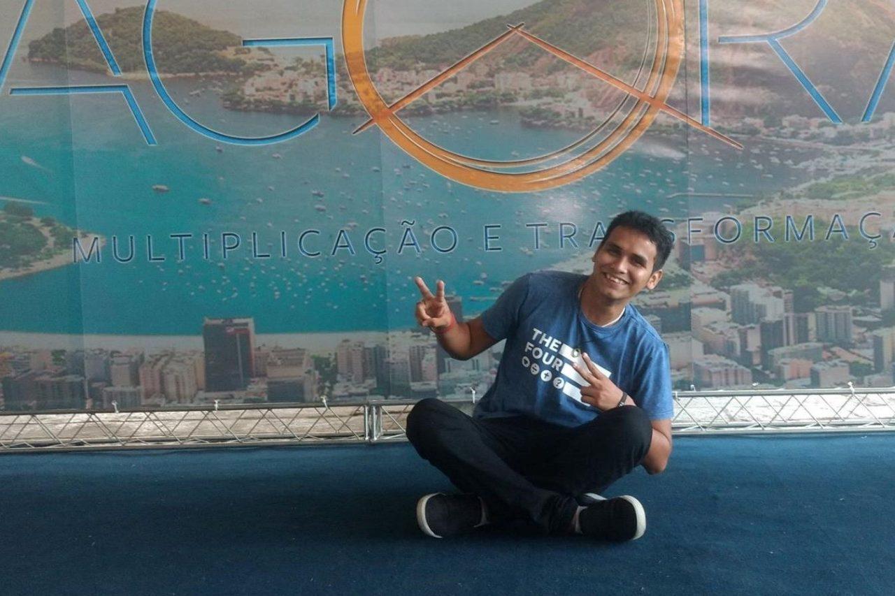 Wilson sorrindo frente ao banner de um congresso da Cru