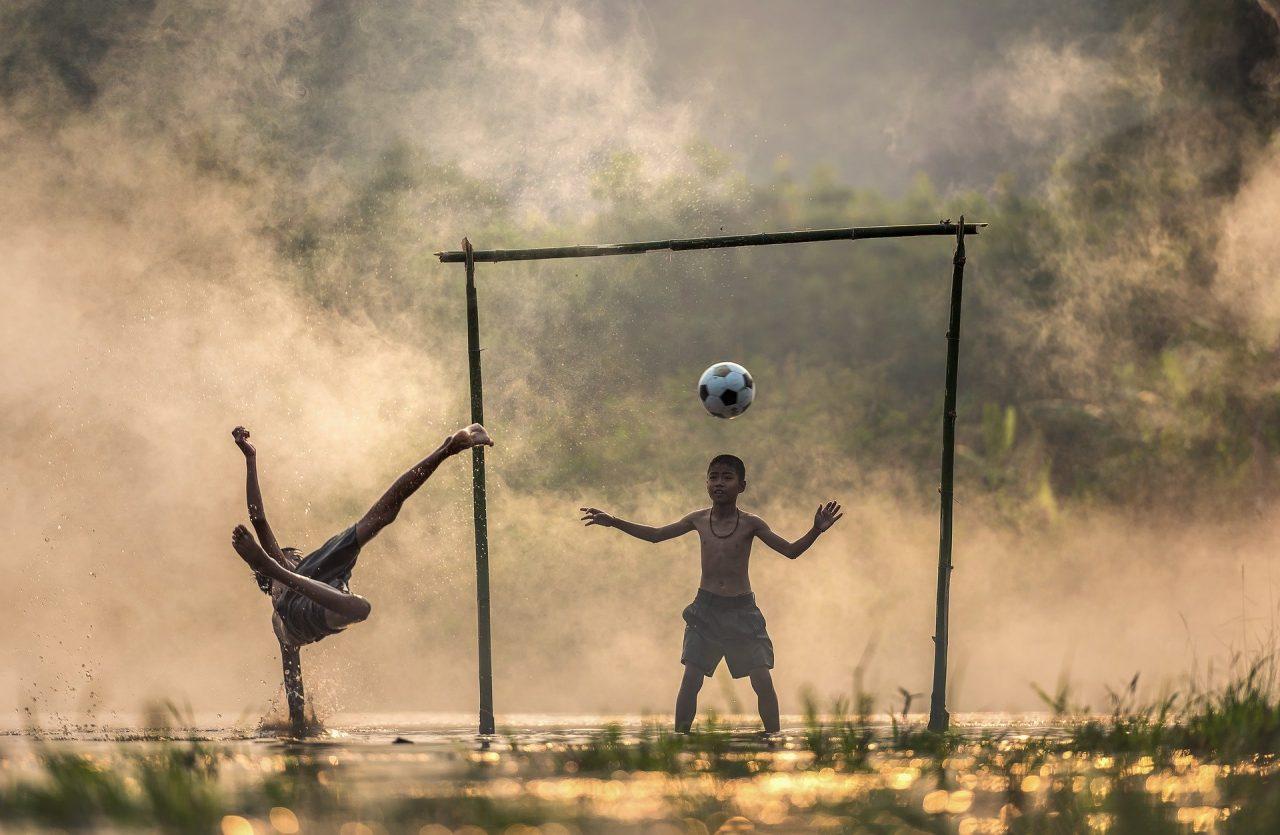 crianças jogando futebol na rua