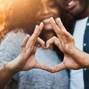 Shot of a a young couple making a heart shape with their fingers outdoors